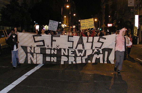 """people marching down geary street with the """"s.f. says no on newsom -- no on prop. m"""" banner as night falls"""