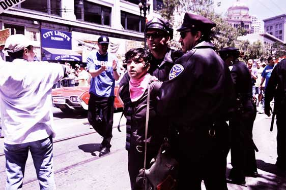 police ushering handcuffed person in pink bandana down market street pride parade route