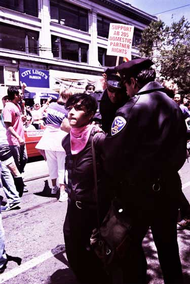 police continue escorting handcuffed person in pink bandana down market street pride parade route