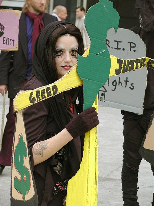 "goth femme mourner holding a cardboard scales with ""greed"" and ""justice"" written on opposite sides and decorated with money signs"