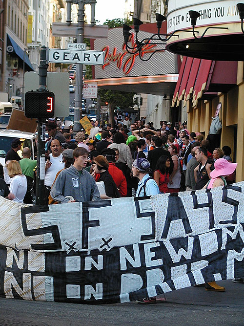 "people gather in front of ruby skye with a ""s.f. says no on newsom -- no on prop m."" banner"