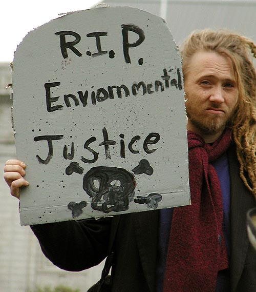 "person holding cardboard tombstone reading ""r.i.p. environmental justice"""