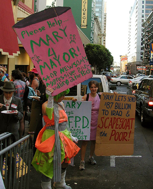 "a group of people holding colorful signs in front of ruby skye reading: ""please help mary 4 mayor! stop newsom's aggressive panhandling 2 the rich,"" ""yay! let's send $87 billion to iraq & scapegoat the poor"" and ""mary says s.f.p.d. makes excellent compost"""