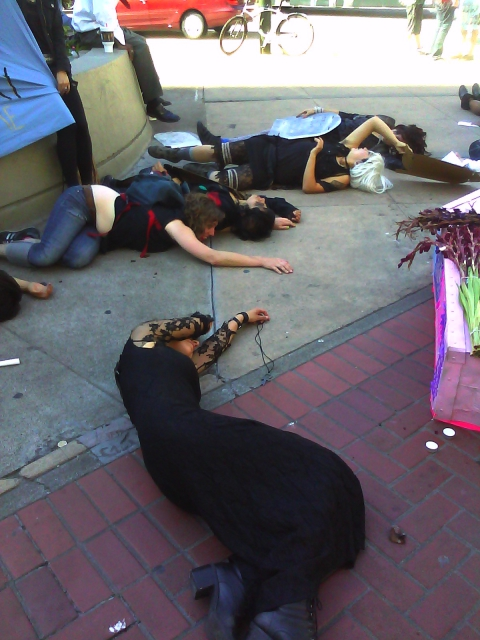 people staging a die-in on the sidewalk in front of the planter by the post office at market and hayes