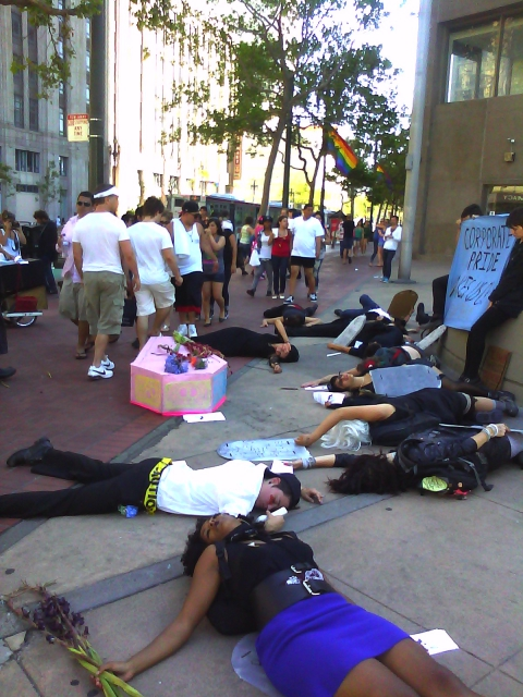 people staging a die-in near the planter in the area in front of the post office at market and hayes