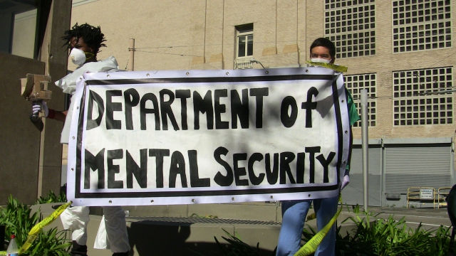 "people holding a banner that says ""department of mental security"""