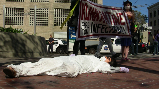"person in a tyvek suit lying on the ground apparently unconscious while people hold a banner in the background reading ""kuarantine are you infected?"" at the corner of market and hayes"