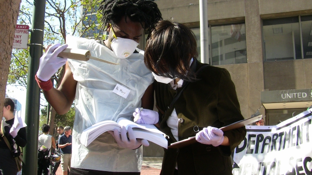 two people are dressed as medical officials examining the dsm and holding a cardboard syringe