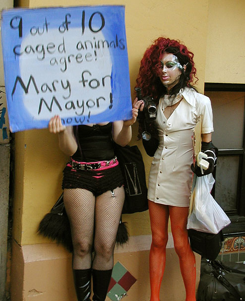 "two people in disguise in front of ruby skye, one holding a video camera and another holding a sign reading ""9 out of 10 caged animals agree! Mary for Mayor!"""