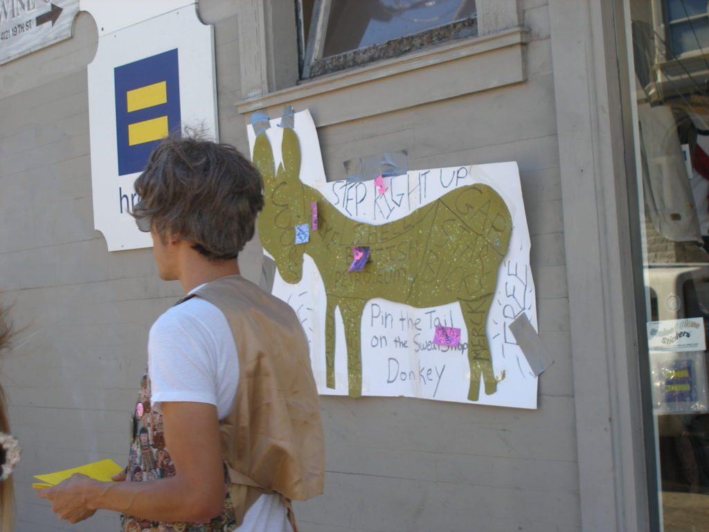 person wearing a wig next to pin the tail on the sweatshop donkey on the exterior of the hrc.org store on castro and 19th