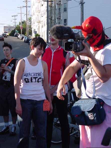 small group of people gathering at buchanan near hermann while a person wearing a red skull fetish mask with horns aims a camcorder