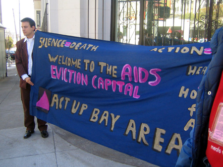 "people holding a navy blue banner in front of the bank of america at 18th and castro that reads ""silence-death action=life health care and housing for all --- welcome to the aids eviction capital -- act up bay area"""