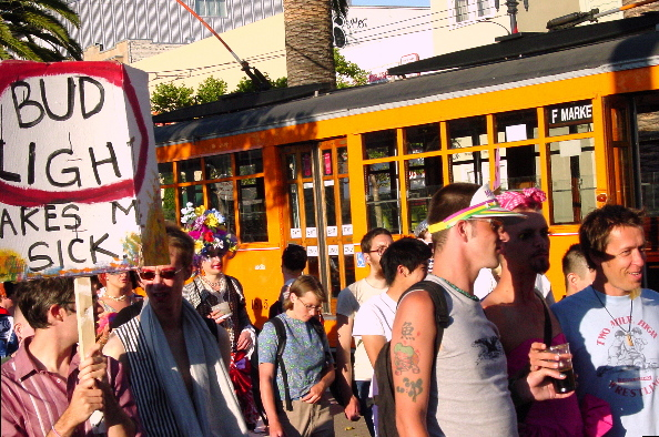 """procession of people heading up market street for the castro, one holding a """"bud light makes me sick"""" sign in the foreground alongside a classic italian street car looming in the background"""
