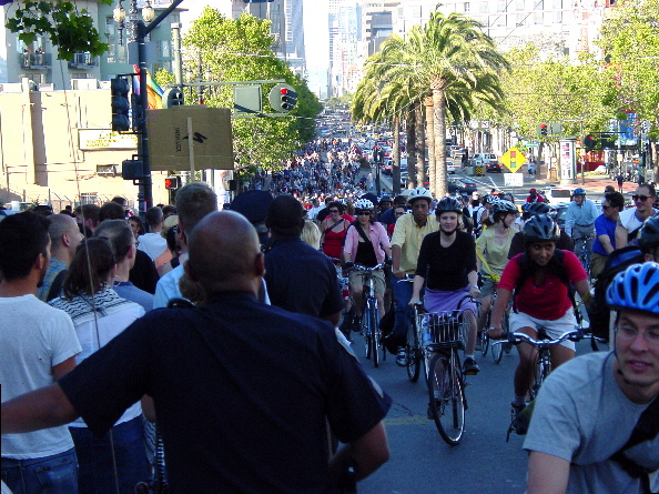 people turning towards a massive crowd of cyclists during a critical mass procession