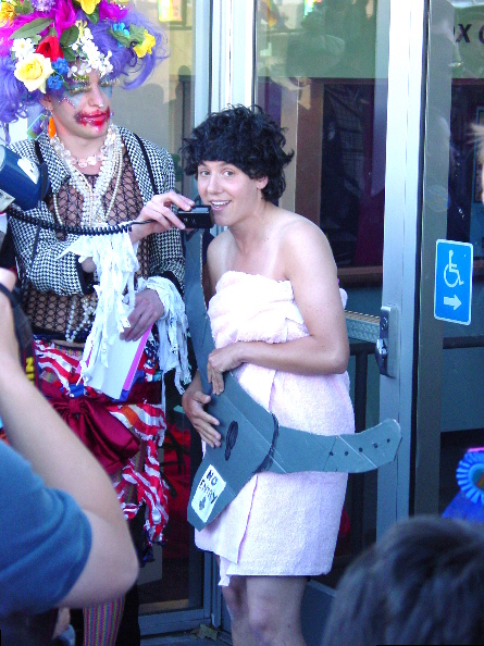 """presentation of the """"contributing to lesbian bed death"""" award in front of the main entrance doors of the lgbt center featuring a person in drag dressed to wretched excess holding the detachable bullhorn microphone for a person dressed as a bathhouse patron wearing a towel covered by a giant cardboard chastity belt labeled """"no entry"""""""