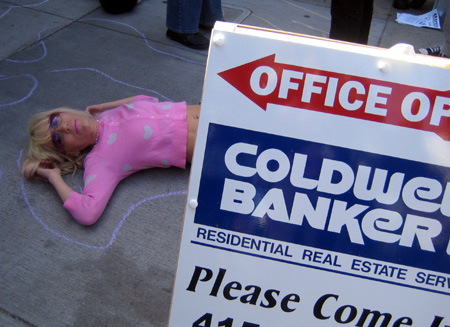 a person doing a die-in laying within a chalk outline in front of the plastic coldwell banker office sandwich board