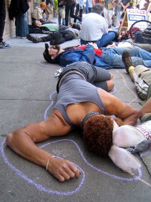 a group of people laying inside their chalk outlines pretending to be dead blocking the sidewalk in front of the new coldwell banker location on market near castro