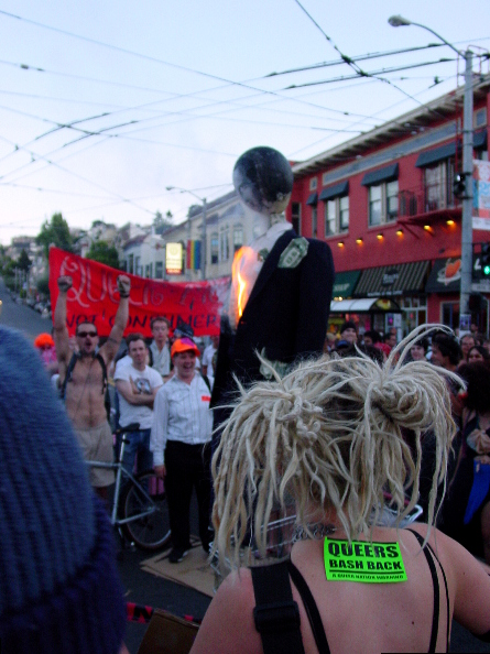 """a crowd of cheering people in the street at castro and 18th with red banner that reads """"queer mutiny not consumer unity"""" in the background surrounding the gavin newsom effigy as it catches aflame with smoke starting to rise. a person wears a fluorescent green """"queers bash back"""" queer nation sticker in the foreground"""