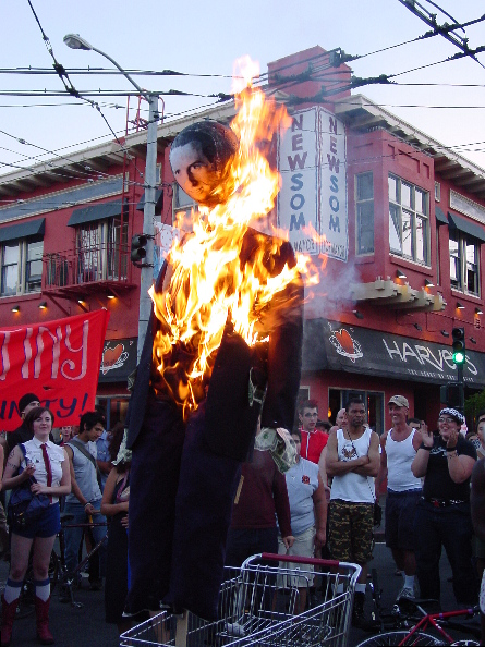 "the flame rises dramatically up the gavin newsom effigy positioned in a shopping cart at the intersection of 18th and castro as people look on with wonder and joy as they stand in the street with the ""gavin newsom for mayor"" sign above harvey's also seeming to silently witness"