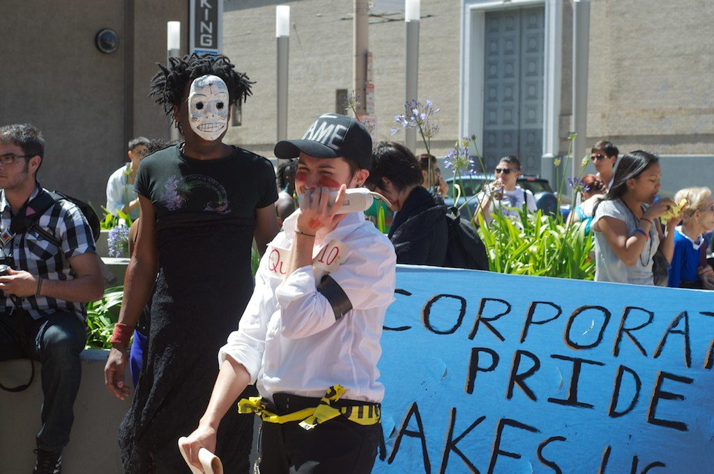 """people gathered on the planter in the post office area at the corner of market and hayes with a blue banner that reads """"corporate pride makes us sad"""""""