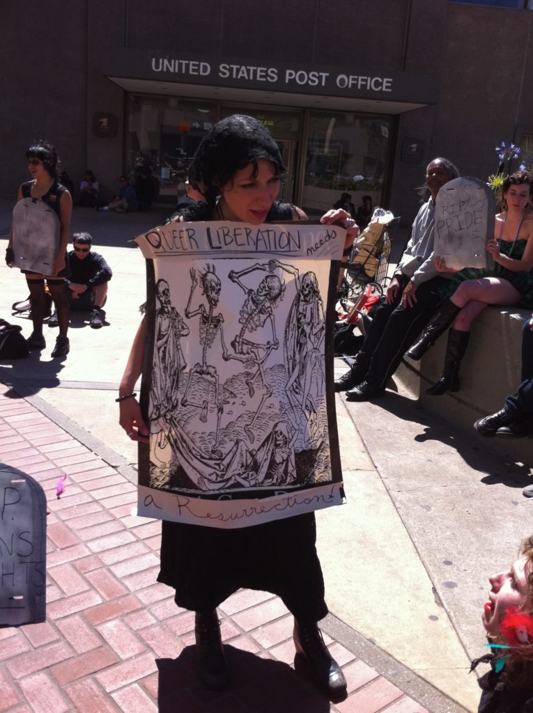 """person holding a sign with dancing skeletons that reads """"queer liberation needs a resurrection"""" in front of the entrance to the post office at market and hayes by the planter"""