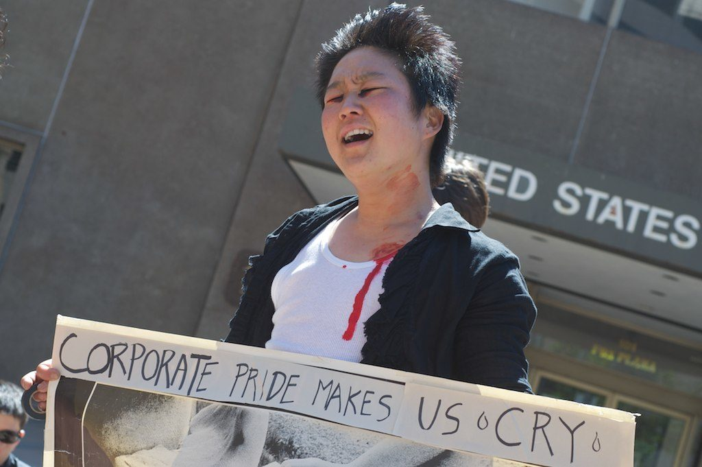 "person sobbing with a sign that says ""corporate pride makes us cry"""
