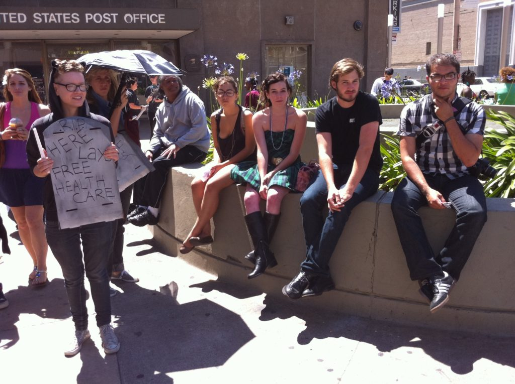 people sitting on the planter in the post office area at market and hayes