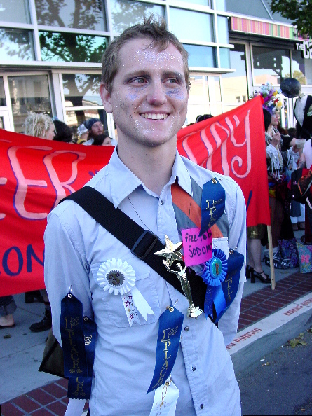 "a medium shot of a person wearing awards ribbons, the red ""queer mutiny not consumer unity"" banner is behind them standing in front of the lgbt center"
