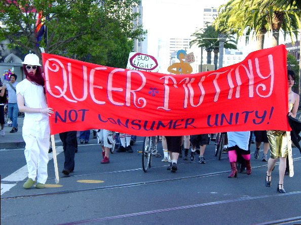 "a view from the front of the procession led by the red ""queer mutiny not consumer unity"" banner"