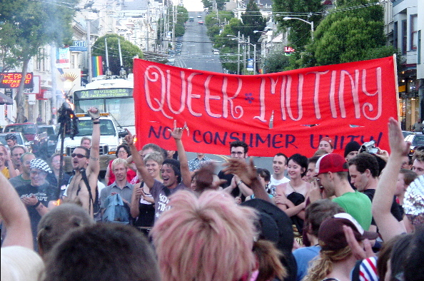 "the crowd cheers as the last of the effigy's smoke rises, the red ""queer mutiny not consumer unity"" banner punctuated the intersection blocked with people as a but sits blocked further up castro street"