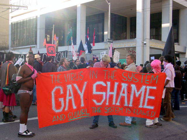 "a gathering of people in pink with a red ""gay shame: a virus in the system -- and guuurl the system is flawed!"" banner in the foreground"