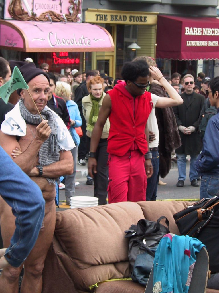 people gather mull about after the awards ceremony into the middle of castro street where a couch has been placed