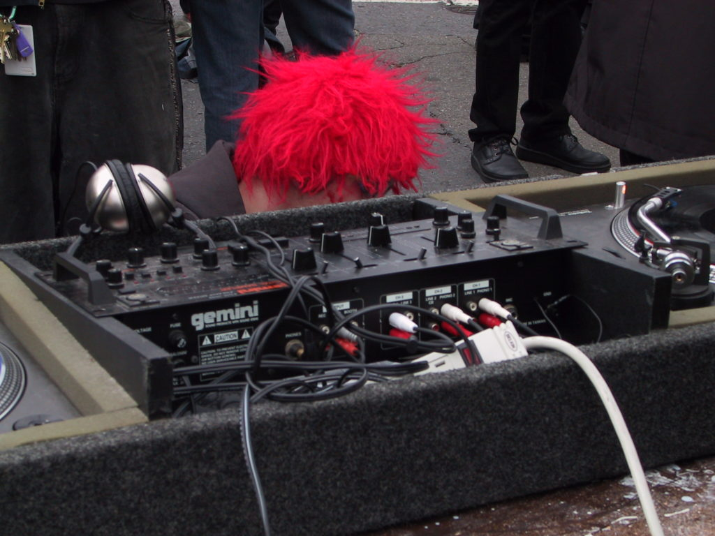 a disc jockey ducks under their table in order to locate the perfect record to serve the crowd at harvey milk plaza after the awards ceremony
