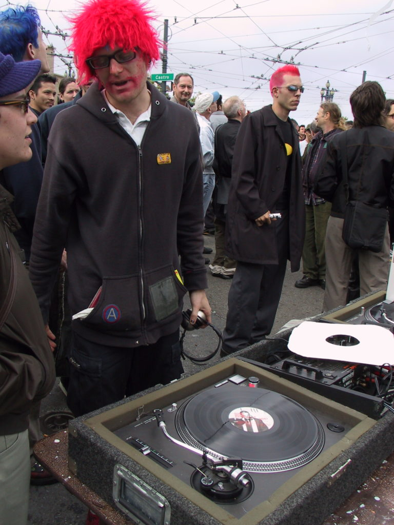 a disc jockey has set up station at a portable sound system as the crowd mulls about in harvey milk plaza after the awards ceremony