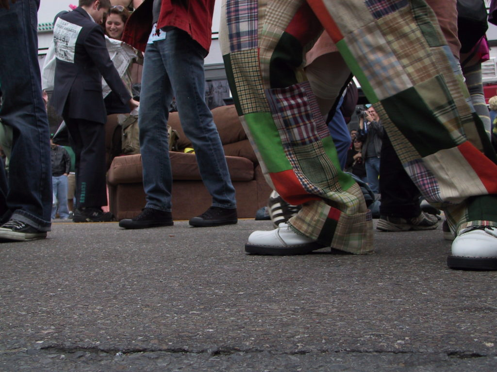 detail of footwear on the asphalt as the crowd fills the middle of castro street with a couch visible in the background