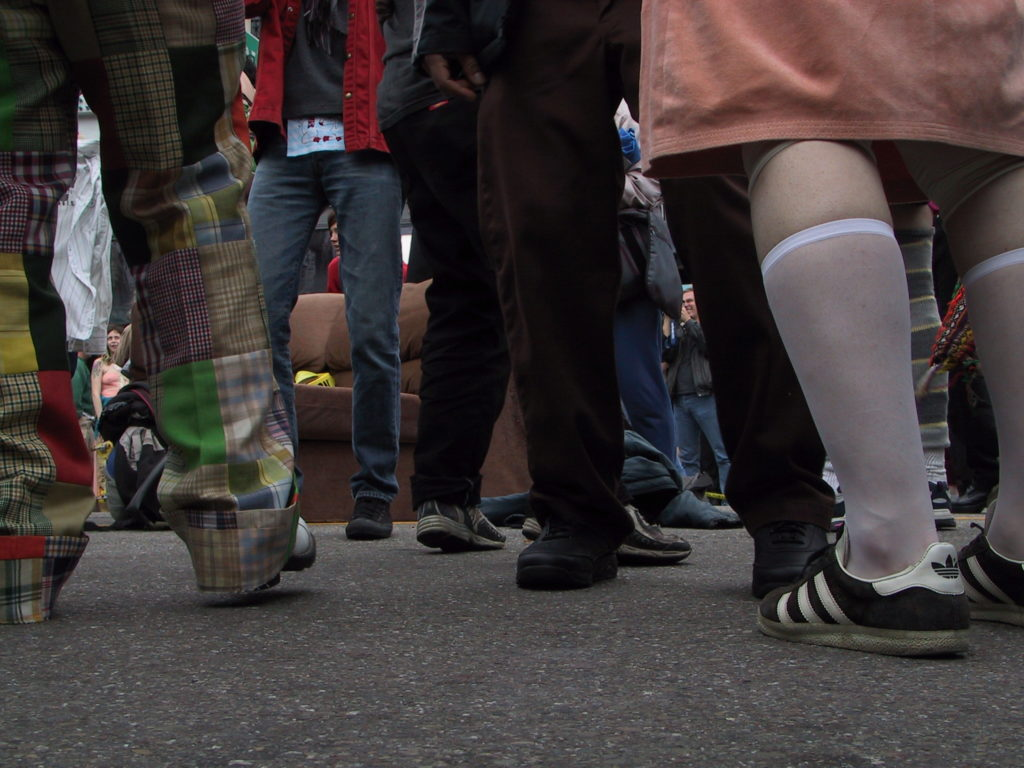 detail of people's outfits from near the asphalt in the middle of castro with a couch visible in the street through the forest of legs