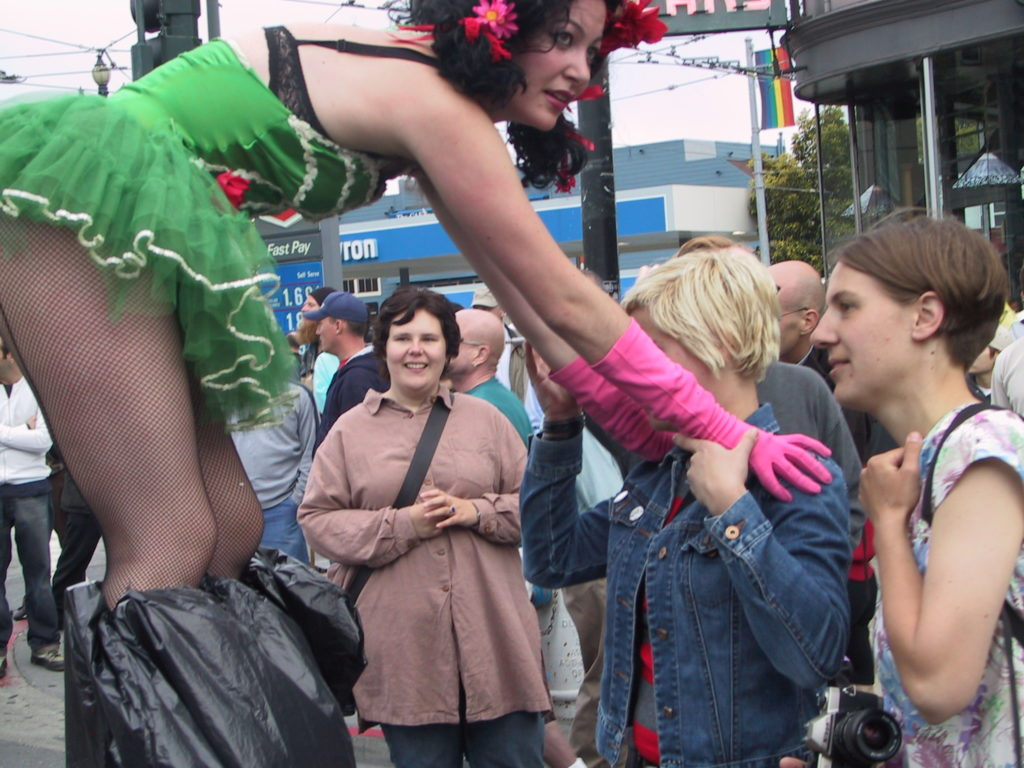 stiltwalkers interact with folks gathering in the street at market and castro