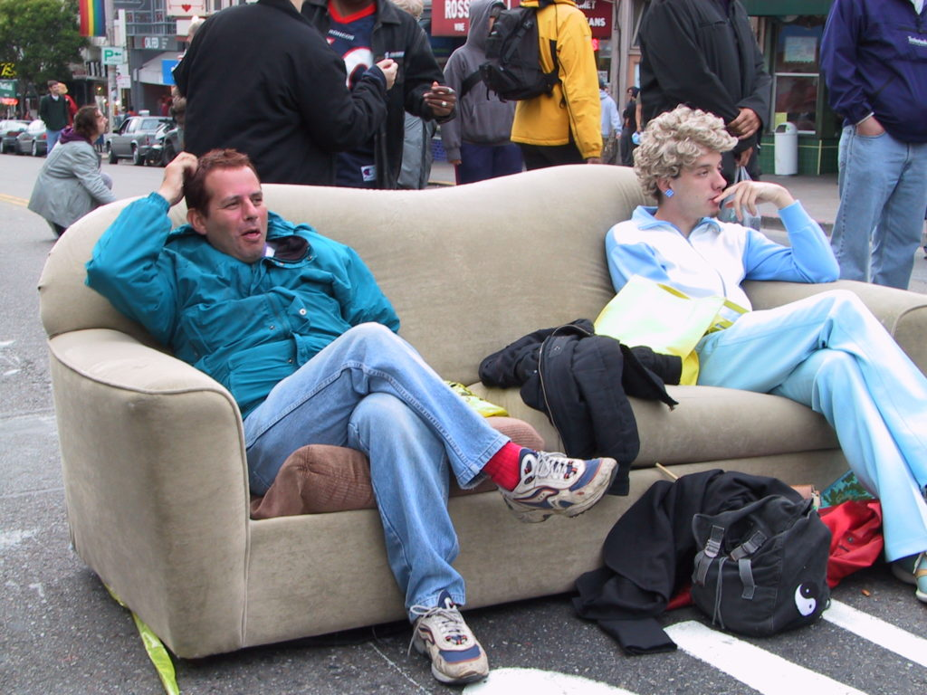 a couch has been drug out into the middle of castro street and awards ceremony attendees take a moment to relax while the dance party starts up