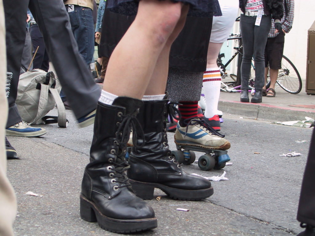 detail of roller skates and other footwear in the middle of castro street