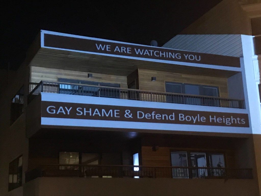 "projections on 55 dolores condo complex at night that reads: ""WE ARE WATCHING YOU -- GAY SHAME & Defend Boyle Heights"""