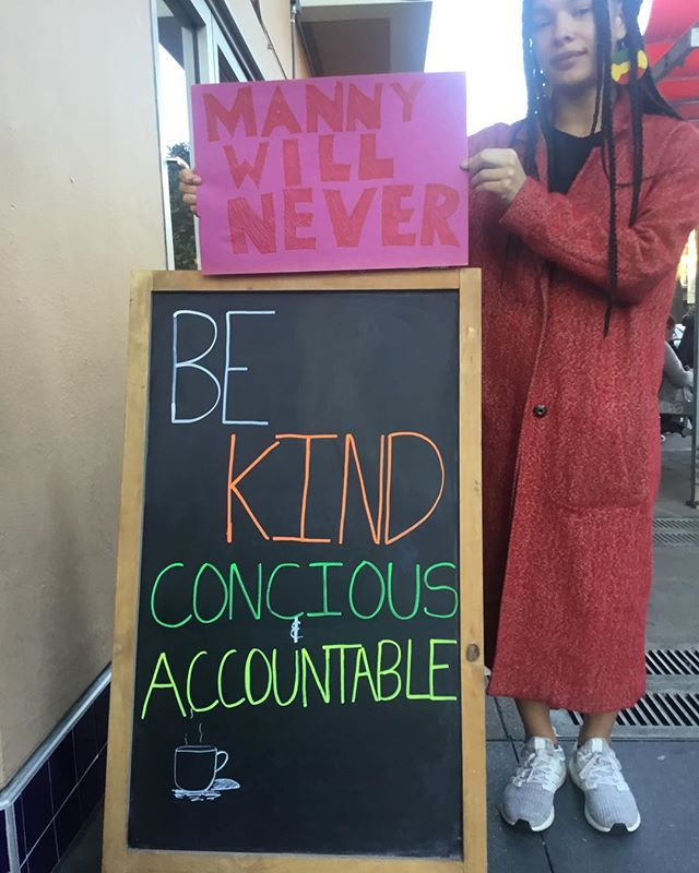 "a person holding a sign reading ""manny will never"" over manny's sandwich board that reads in chalk ""be kind concious & accountable"""