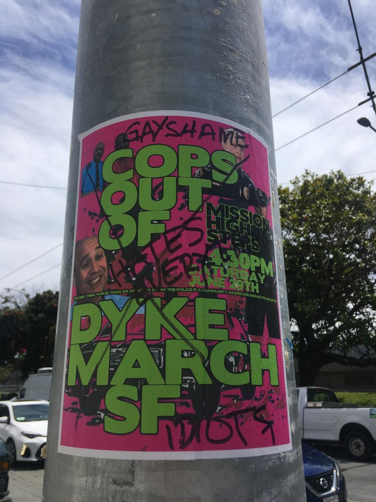 "a ""cops out of dyke march"" poster on a pole that has been crossed out and graffiti'd with ""gay shame hates everything -- idiots"""
