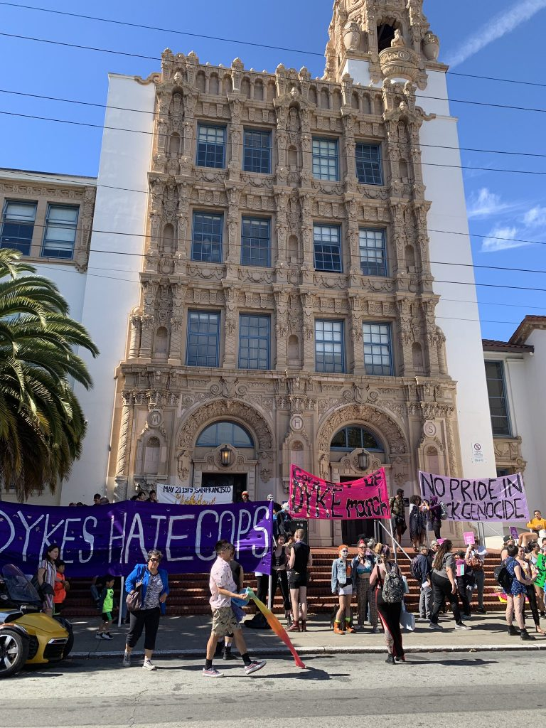"""banners on display on the 18th street front entrance steps of mission high reading """"dykes hate cops"""" """"cops out of the dyke march"""" and """"no pride in genocide"""""""