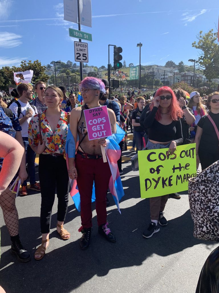 """people gathering in the intersection, one with a sign that says """"cops out of the dyke march"""" and """"dykes say cops get out"""""""