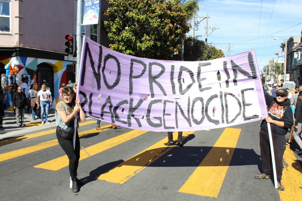 "two people holding a lavender banner at 18th and dolores that reads ""no pride in black genocide"""
