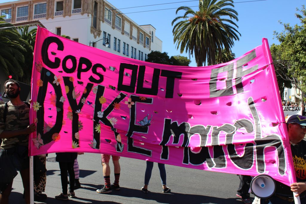 "people holding a bright pink satin banner at 18th and dolores that says ""cops out of dyke march"""