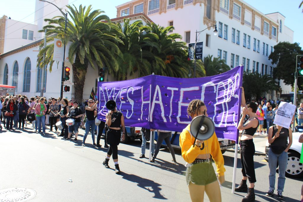 "people hold the intersection at 18th and dolores in front of mission high with a purple satin banner reading ""dykes hate cops"""