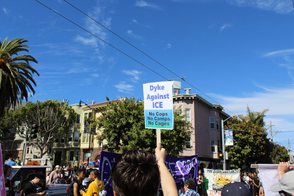 """people are in the intersection at 18th and dolores with a sign that says """"dykes against ice -- no cops no camps no cages"""""""