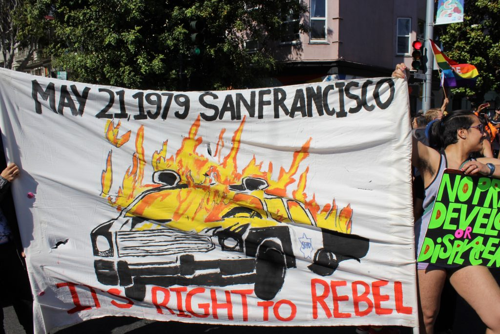 "people holding a banner with a burning cop car that reads ""may 21, 1979 -- it's right to rebel"""