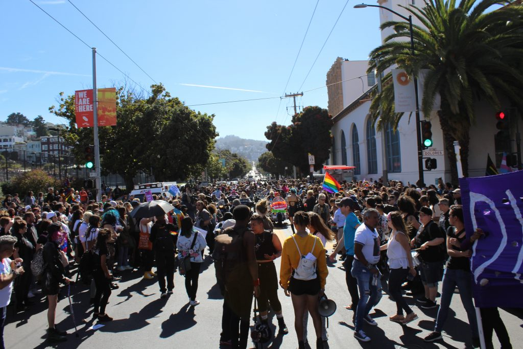 people filling the intersection at 18th and dolores as the dyke march is about to begin